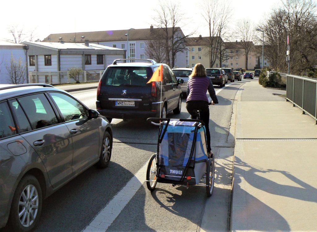 Radlerin fährt am Auto-Stau vorbei, Weilheim