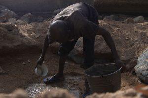 Dokumentarfilm 'Klimafluch und Klimaflucht' - Afrikaner graebt nach Wasser